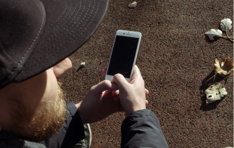 Un bărbat mai în vârstă care se uită la imagini de captare a telefonului cu copii